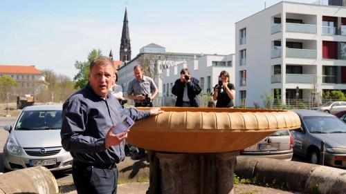 Uwe Ostmann erläutert der versammelten Presse, die Reparatur des Brunnens - Anklicken zum Vergrößern
