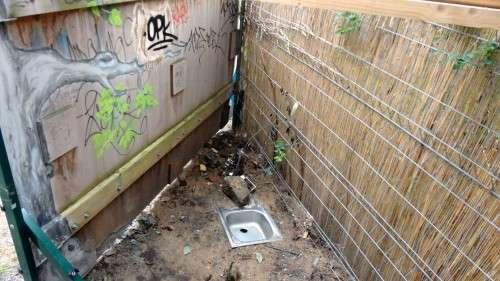 Provisorische Toilette hinter der Plakatwand.