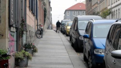 Mit Schwung wird die Straße gekehrt.