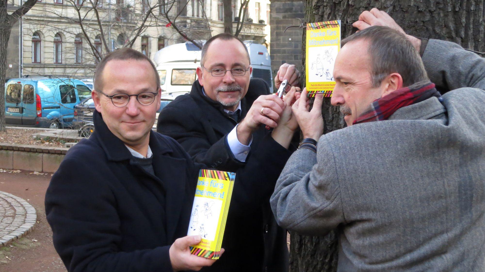 Pfarrer, Ortsamtsleiter und Grünflächen-Chef hängen eine Tafel auf.