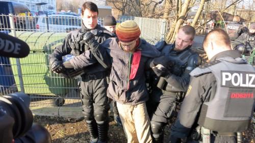 Polizisten führen einen Blockierer ab.
