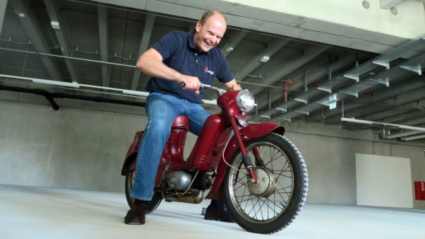 Das erste Exponat ist schon da. Peter Simmel hat sichtlich Spaß mit dem Moped.