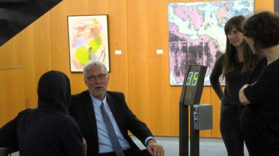 Bank-Sprecher Dieter Hoefer auf Bankautomat, daneben die Künstlerinnen Winnie Seifert und Marie Athenstaedt.
