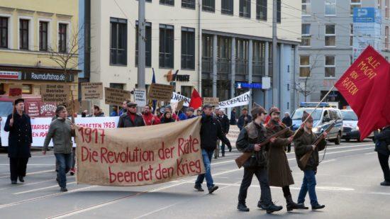 Demo mit Waffen und Transparenten.