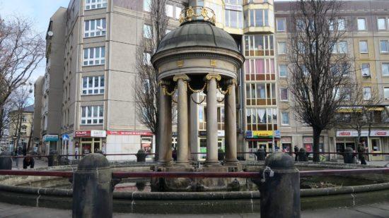 Artesischer Brunnen mit Wasserbecken.