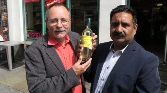 Spät-Shop-Chef Khalid Mazhar und Ortsamtsleiter André Barth mit beklebter Weinflasche.