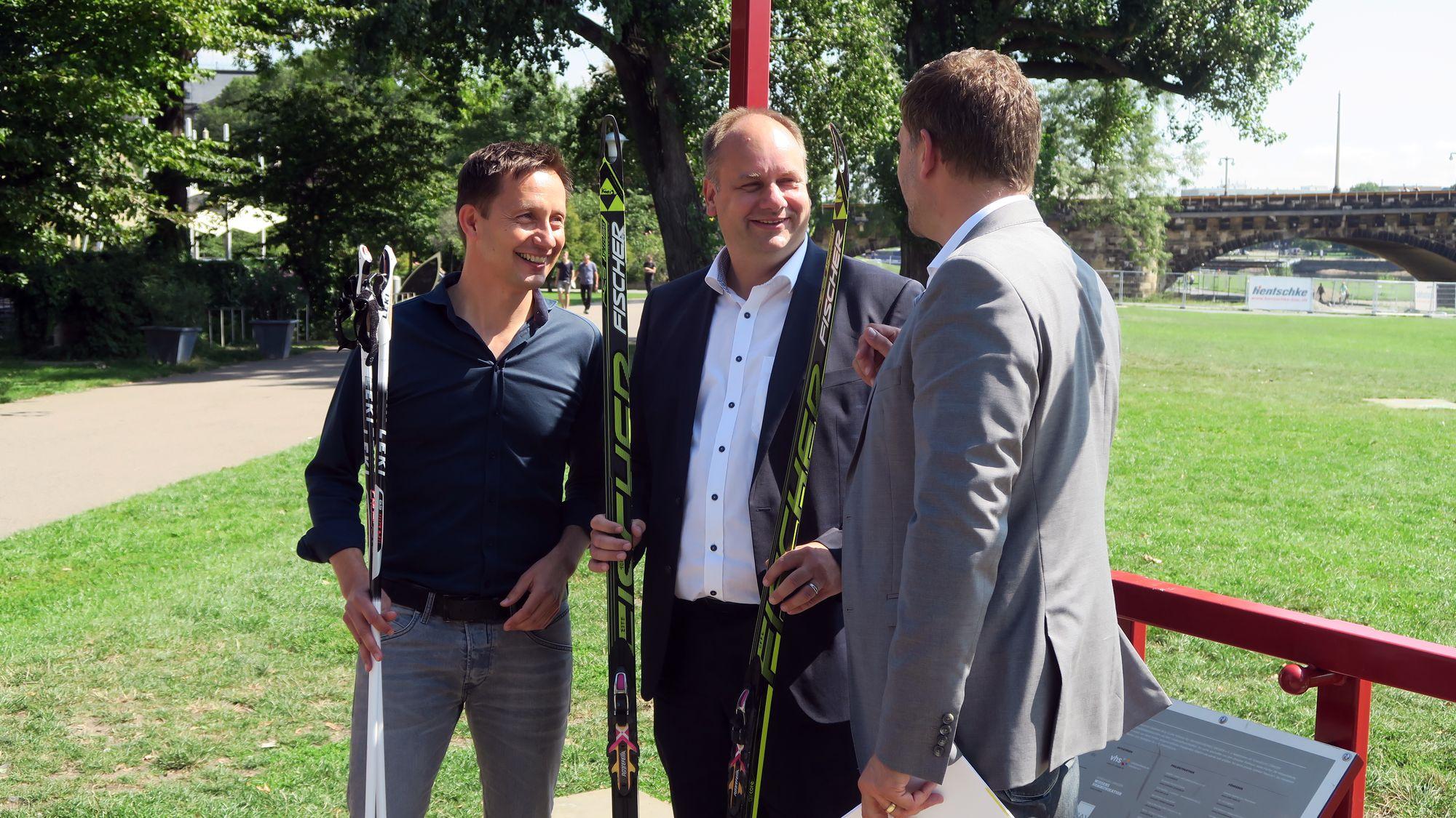 Drei Männer mit Ski. Die Moderatoren Torsten Püschel und René Kindermann hatten passende Langläufer für OB Hilbert dabei.