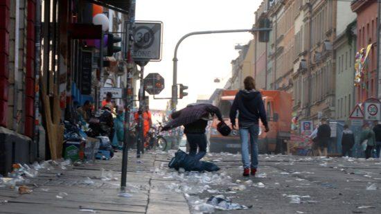 Beherzt springt der junge Mann auf einen prallen Mülleutel, bis er platzt.