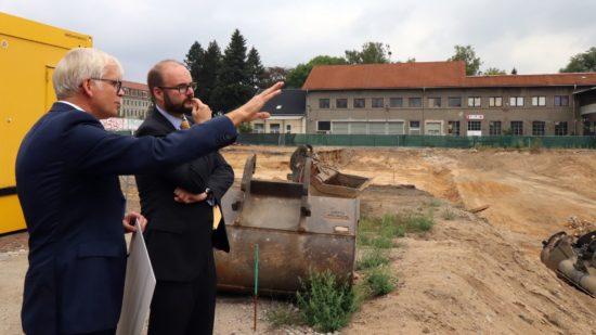 Schulbürgermeister Vorjohann erläutert dem Kultusminister den geplanten Schulneubau. Im Hintergrund das Haus Sieben, das im Frühjahr abgerissen werden soll.