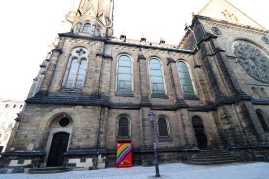 Ein Farbtupfer vor der grauen Kirche.