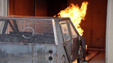 Das Auto in der Garage brennt.