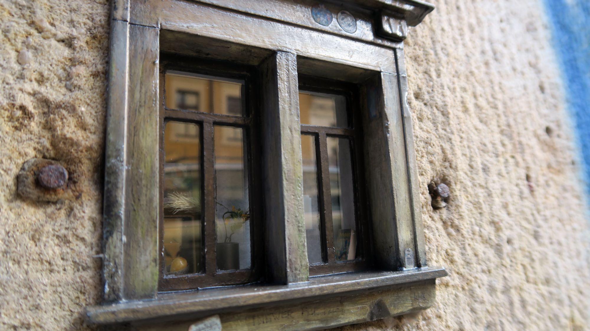 Im Fenster spiegeln sich die Häuser der gegenüberliegenden Straße.
