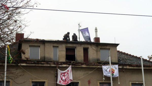Die Polizei holt einen Besetzer vom Dach.