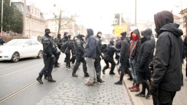 Die Polizei schuppt die Portestierenden zurück auf den Gehweg.