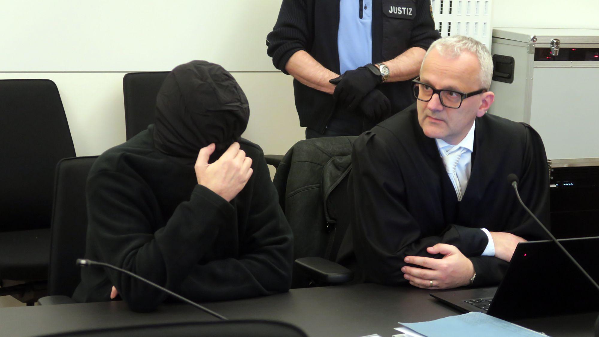 Zum Prozessauftakt verhüllte sich der Angeklagte komplett, neben ihm sein Anwalt Andreas Boine