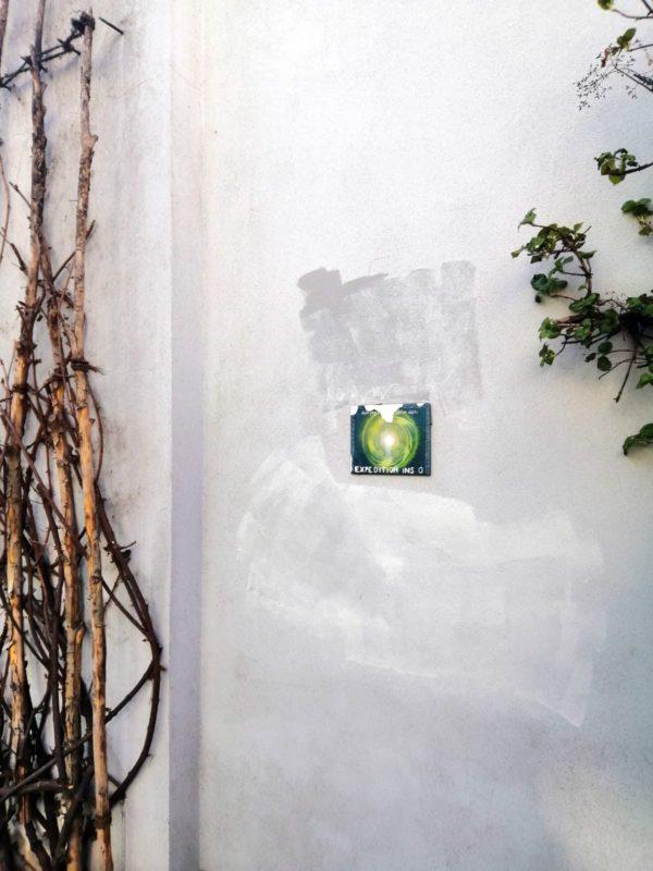 Grüne Fliese auf grauer Wand.