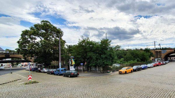 Hinter den Bäumen befindet sich aktuell ein Parkplatz und ein kleines Haus.