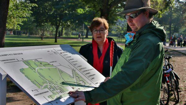 Jan Blüher testet die Infotafel - im Hintergrund: Halina Starkloff vom Grünflächenamt.