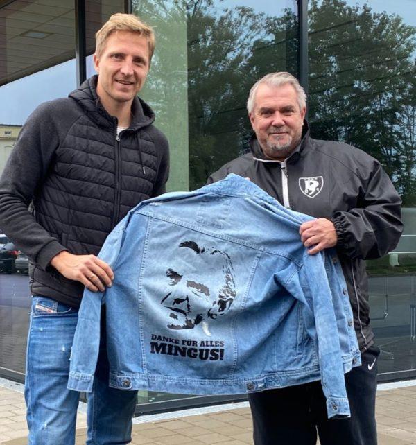 Dynamo-Spieler Marco Hartmann (links) und Sportfreunde-Geschäftsführer Maik Hebenstreit mit der Jacke von Ralf Minge.
