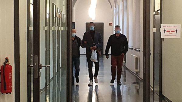 Der Angeklagte (Mitte) wird zum Verhandlungssaal gebracht.