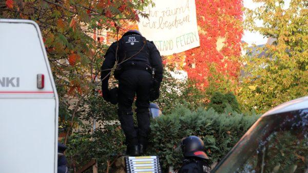 Mehrere Polizisten klettern über den Zaun auf das Grundstück.