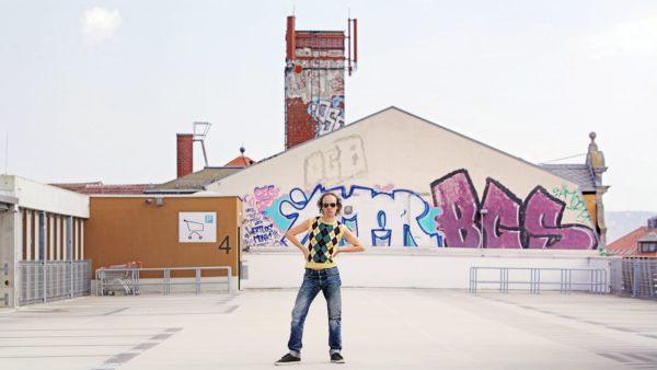 Steigt den Symbolen des Kapitalismus (Parkhaus, Supermarkt, Drogerie) aufs Dach: Autor Olaf Schubert. Foto: Amac Garbe