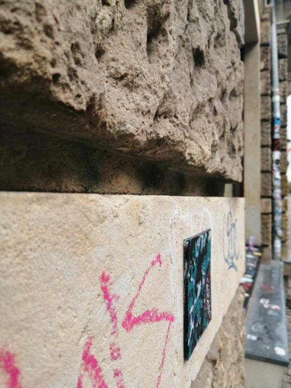 Kleine Fliese an Sandsteinwand.