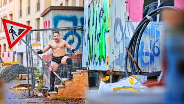 Wrestler Laurenz Domschke mit Bauarbeiterschild auf der Prießnitzstraße - Foto: Amac Garbe