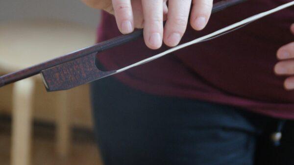 Die Haare dieser alten Violine werden mit einem Stück Holz, dem Steckfrosch, gespannt. Er wird vor dem Spiel eingeklemmt. Foto: Philine