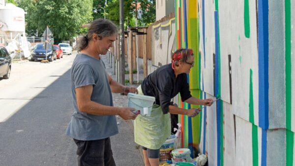 Claudia Scheffler mit einem Helfer beim Reparieren des Wandbildes - Foto: Peter Zuber