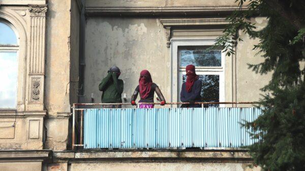 Hausbesetzer*innen auf dem Balkon